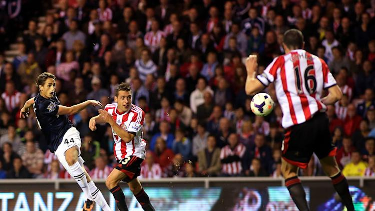 Manchester United's Adnan Januzaj, left, scores his goal past Sunderland's captain John O'Shea, right, during their English Premier League soccer match at the Stadium of Light, Sunderland, England, Saturday, Oct. 5, 2013. (AP Photo/Scott Heppell)
