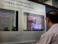 An investor monitors share prices at a bank in Singapore, 2008. Singapore's stock exchange will impose stricter admission rules for initial public offerings (IPOs) to woo bigger brand name companies to list on its bourse
