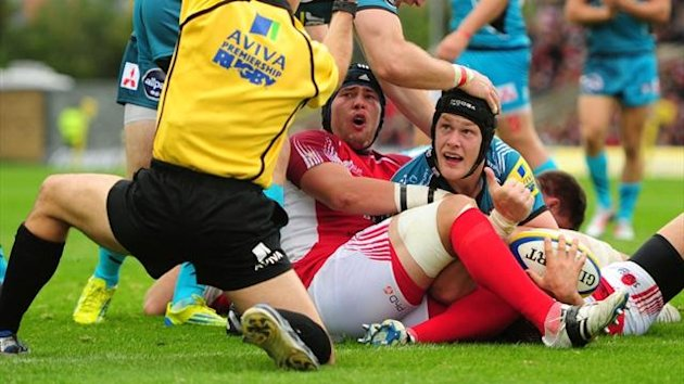 Gloucester's Tom Savage (skull cap) looks to the referee after scoring a try against London Welsh