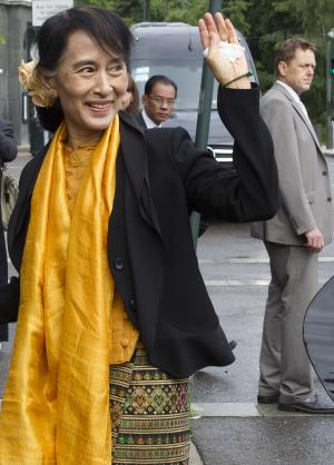 Myanmar opposition leader Aung San Suu Kyi waves as she arrives at the Foreign Ministry for a meeting with Norway's Foreign Minister Jonas Gahr Store in Oslo, Sunday, June 17, 2012. Myanmar opposition leader Aung San Suu Kyi said Saturday at a Nobel Prize lecture that the Nobel Peace Prize she won while under house arrest 21 years ago helped to shatter her sense of isolation and ensured that the world would demand democracy in her military-controlled homeland. (AP Photo/Markus Schreiber)