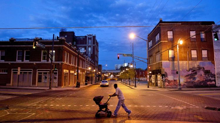 A man pushes a stroller across Auburn Avenue, Thursday, June 7, 2012, in Atlanta. Today Auburn Avenue is a shell of its former self, the bustling mix of banks, night clubs, churches, meat markets and funeral homes long gone, replaced with crumbling facades and cracked sidewalks. Hundreds of thousands of people still flock to Auburn Avenue to see King's birth home, the church where he preached and the crypt where he and his wife, Coretta, are buried. But tourists have little reason to linger. While King's legacy has been preserved, Auburn Avenue's business community has never recovered from the exodus of the black community that supported it. This week, the area was placed on the National Register of Historic Places' 11 Most Endangered list for the second time since 1992 in hopes of spurring preservation-oriented development. (AP Photo/David Goldman)