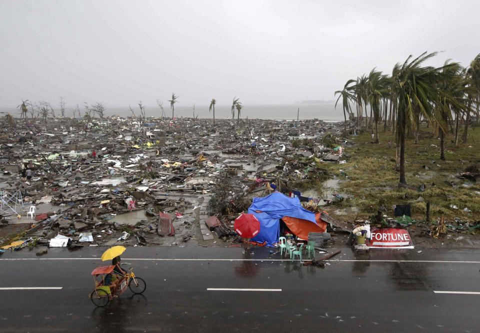 Residents walk past the devastation caused by Typhoon Haiyan, Sunday, Nov. 10, 2013, in Tacloban city, Leyte province in central Philippines. Typhoon Haiyan, one of the strongest storms on record, slammed into six central Philippine provinces Friday leaving a wide swath of destruction and hundreds of people dead. (AP Photo/Bullit Marquez)