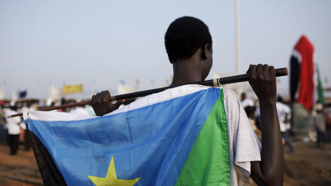 A youth holds the flag of South Sudan as he waits for the start of independence celebrations in Juba, South Sudan, Saturday, July 9, 2011. South Sudan raised the flag of its new nation for the first time on Saturday, as thousands of South Sudanese citizens swarmed the capital of Juba to celebrate the country's birth. (AP Photo/David Azia)