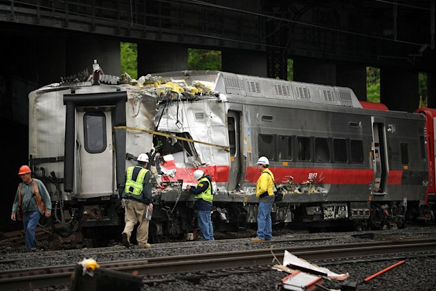Metro-North employees work at the site of Friday's train derailment in Bridgeport. Conn. on Sunday, May 19, 2013. Crews will spend days rebuilding 2,000 feet of track, overhead wires and signals follo