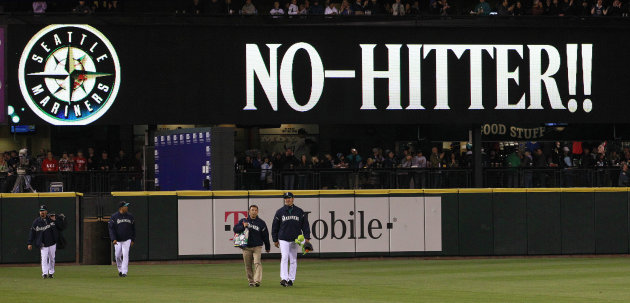 "Seattle Mariners head in from the bullpen as a sign flashes ""No-Hitter!!"" behind after a baseball game against the Los Angeles Dodgers Friday, June 8, 2012, in Seattle. The Mariners won 1-0 in a six-pitcher combined no-hitter. (AP Photo/Elaine Thompson)"