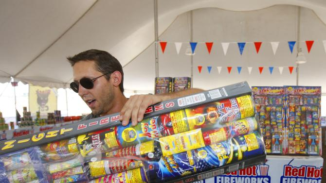 In this photo taken on Wednesday, July 2, 2014, Brian Herrman, a co-owner of Red Hot Fireworks in Phoenix, puts out new items on the shelves as sales of fireworks have been brisk at the store. Although Phoenix has gone a full 120 days without any measurable precipitation there has not been any serious effort in the drought-stricken states to restrict fireworks. Arizona actually loosened its restrictions this year and allowed residents of the two most populated cities to set off fireworks around Independence Day. (AP Photo/Ross D. Franklin)