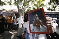 A fan holds a photo of late singer Michael Jackson and a white glove outside Los Angeles Superior Court following the verdict in the Jackson vs AEG Live trial, in Los Angeles, California October 2, 2013. REUTERS/Mario Anzuoni