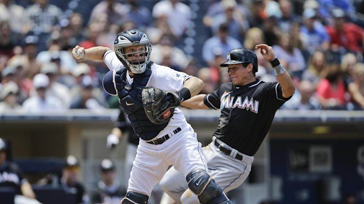 San Diego Padres catcher Nick Hundley relays to first to complete an inning ending double play after getting the force out at home on MIami Marlins' Derek Dietrich in the third inning of a baseball game in San Diego, Wednesday, May 8, 2013. The Marlins' Adeiny Hechavarria was out at first. (AP Photo/Lenny Ignelzi)