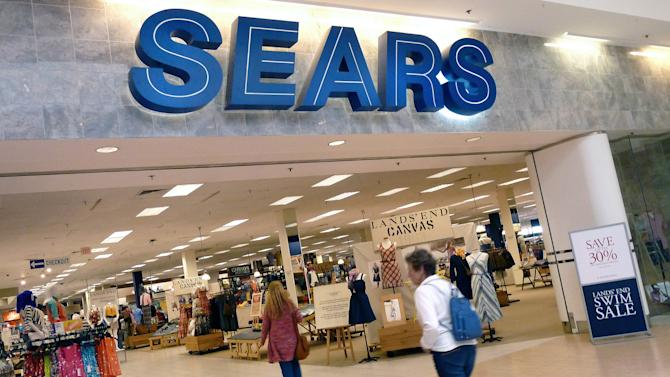 FILE - In this Monday, May 14, 2012, file photo, shoppers walk into Sears in Peabody, Mass. Sears is considering separating its Lands' End and Sears Auto Center businesses from the rest of the company. The retailer also plans to continue closing some of its unprofitable stores as it moves forward on its turnaround efforts, the company announced Tuesday, Oct. 29, 2013. (AP Photo/Elise Amendola, File)