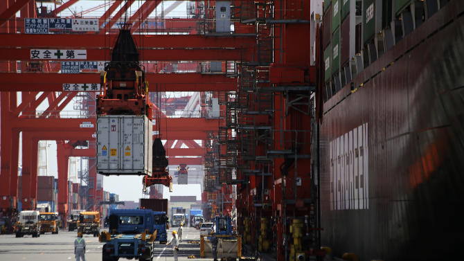 A cargo is unloaded from a truck to load onto a freight vessel at the pier of a container terminal in Tokyo, Wednesday, Aug. 20, 2014. Japan's trade deficit rose in July from the month before to a wider than expected 964 billion yen ($9.4 billion), though exports were higher for the first time in three months, the government said Wednesday. (AP Photo/Eugene Hoshiko)
