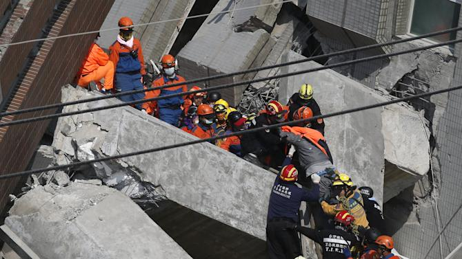 Rescuers carry a 20-year-old male survivor out from the site where a 17-storey apartment building collapsed after an earthquake hit Tainan,