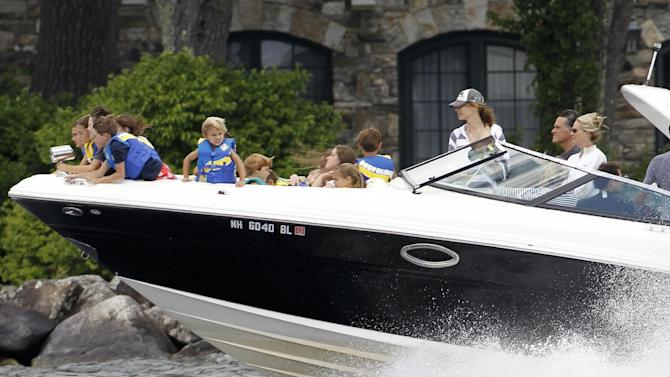 """FILE - In this July 5, 2012, photo Republican presidential candidate Mitt Romney, at right next to his wife Ann, drives his boat out of his vacation home with his grandchildren seated on the bow on Lake Winnipesaukee in Wolfeboro, N.H. Romney's large family is at the center of his life _ and of his presidential campaign. At a time when nontraditional families have become the norm _ and when even the Romneys are watching """"Modern Family,"""" a popular sitcom that centers on unconventional family arrangements _ the Romney brood stands out. (AP Photo/Charles Dharapak, File)"""