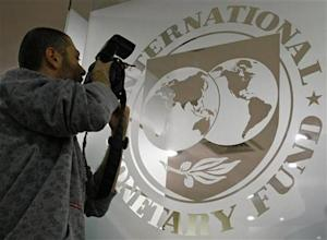 A photographer takes pictures through a glass carrying the International Monetary Fund logo during a news conference in Bucharest