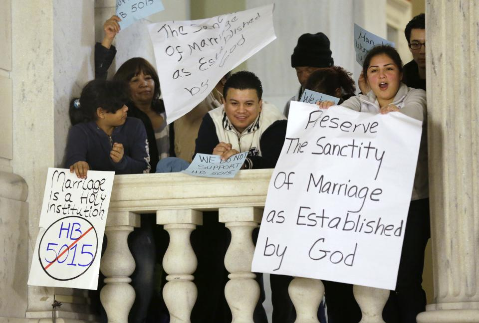Demonstrators display placards and shout slogans as they voice their opposition to same-sex marriage during a rally at the Statehouse, in Providence, Tuesday, Jan. 15, 2013. The Rhode Island House Judiciary Committee began hearing testimony from supporters and opponents of same-sex marriage Tuesday. (AP Photo/Steven Senne)