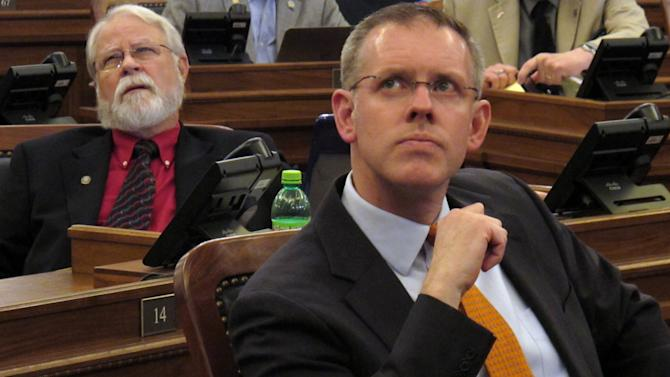 Kansas House Minority Leader Paul Davis, right, a Lawrence Democrat, watches the chamber's electronic tally board and listens to a reading of the names of victims of the mass shooting at a Newtown, Conn., as the House votes on gun-rights legislation, Friday, April 5, 2013, at the Statehouse in Topeka, Kan. Behind Davis and to his left is Rep. Ed Timmer, a Winfield Democrat. (AP Photo/John Hanna)