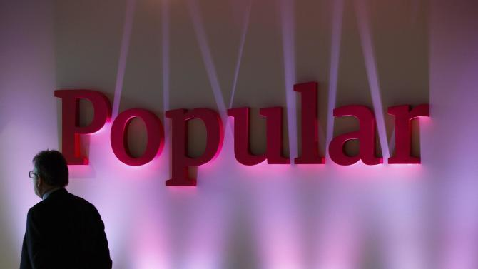 A man stands next to the logo of Spain's Banco Popular during the bank's results presentation in Madrid