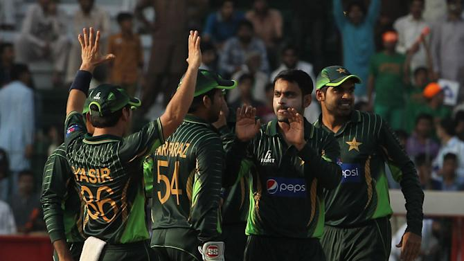Pakistani players celebrate the dismissal of   Zimbabwe's Vasimuzi Sibanda during a match in Lahore, Pakistan, Friday, May 29, 2015. Pakistan won the toss and chose to bowl in the second one-day international against Zimbabwe on Friday. (AP Photo/K.M. Chaudary)