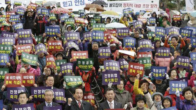 """South Korean protesters from Korea Freedom Federation shout slogans during a rally denouncing North Korea's decision to pull workers from the Kaesong industrial park, as well as its threat of nuclear war and its alleged plan to launch a missile, in Seoul, South Korea, Thursday, April 11, 2013. The letters read """"Stop immediately War threat.""""   Bracing for what South Korea's foreign minister warned could be a test-fire of a medium-range missile, Seoul deployed three naval destroyers, an early warning surveillance aircraft and a land-based radar system, a Defense Ministry official said in Seoul. (AP Photo/Lee Jin-man)"""