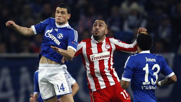 Schalke 04's Kyriakos Papadopoulos and Olympiakos' Kostas Mitroglou (R) head a ball during their Champions League Group B match