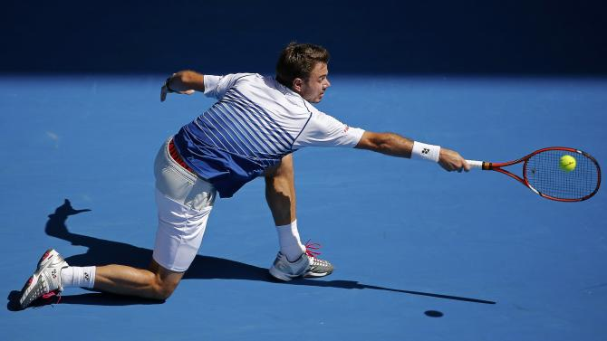 Wawrinka of Switzerland stretches to hit a return to Nishikori of Japan during their men's singles quarter-final match at the Australian Open 2015 tennis tournament in Melbourne