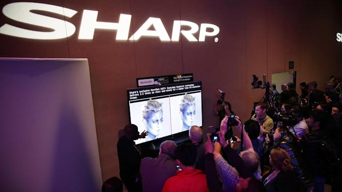 Journalists check out the new Sharp 4K lite television during a news conference at the Consumer Electronics Show press day on Monday, Jan. 6, 2014, in Las Vegas. (AP Photo/Isaac Brekken)