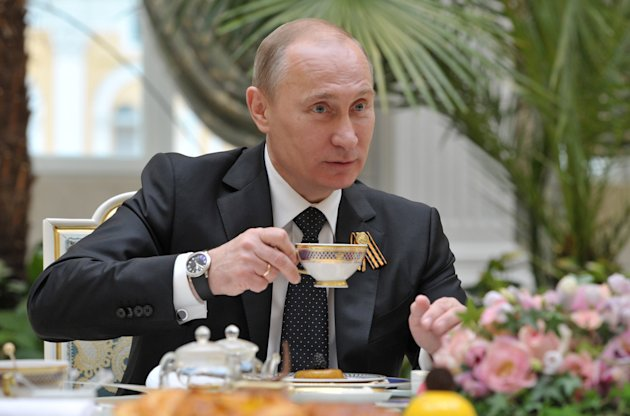 Russian President Vladimir Putin holds a cup of  tea as he meets with Sonya, 8, not pictured, from the city of Pskov in Moscow's Kremlin on Wednesday, May 9, 2012. Sonya undergoes a medical treatment