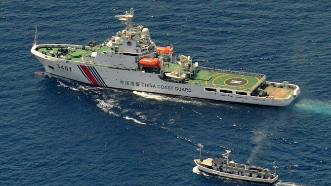 A China Coast Guard ship (top) and a Philippine supply boat engage in a stand off on March 29, 2014 as the Philippine vessel attempts to reach the Thomas Shoal, a remote reef in the South China Sea that is claimed by both countries