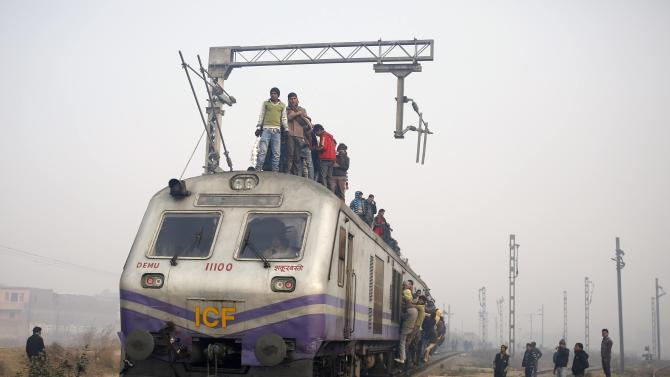 Passengers crowd atop a train as they travel on a cold winter morning at a railway station in Ghaziabad