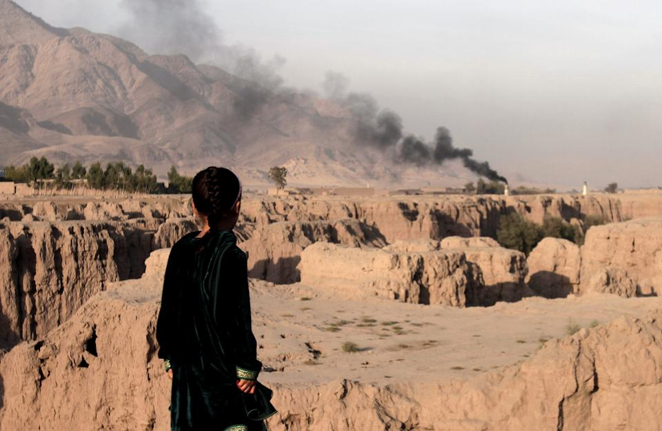 An Afghan girl looks over a ravine toward smoke rising from a brick factory chimney in Surkh Rod district, Jalalabad east of Kabul, Afghanistan, Tuesday, Oct. 30, 2012. (AP Photo/Rahmat Gul)