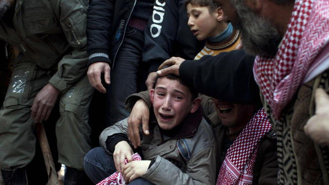 FILE - Ahmed, center, mourns his father Abdulaziz Abu Ahmed Khrer, who was killed by a Syrian Army sniper, during his funeral in Idlib, north Syria, Thursday, March 8, 2012. (AP Photo/Rodrigo Abd, File)