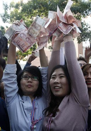 Anti-government protesters hold Thai banknotes to donate to their leader Suthep Thaugsuban during a rally at a major business district in Bangkok