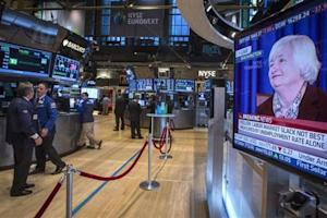 A screen displays a news conference by Federal Reserve Chair Janet Yellen as traders work on the floor of the New York Stock Exchange
