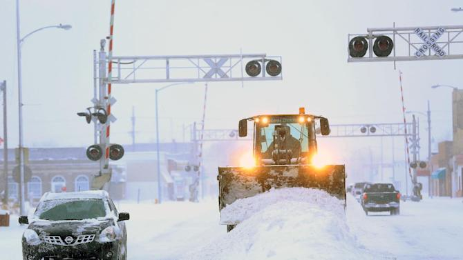 A City of Hutchison, Kan., front end loader clears snow from intersections on S. Main St. Tuesday, Feb. 4, 2014. The winter storm dumped more than 10 inches of snow on the city from late Monday to late Tuesday. (AP Photo/The Hutchinson News, Travis Morisse)