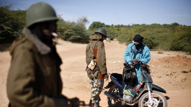 Malian soldiers check  identity papers at a checkpoint set on the outskirt of Diabaly, Mali,  some  460kms (320 miles) north of the capital Bamako Monday Jan. 21, 2013.  French and Malian troops were in the city whose capture by radical Islamists prompted the French military intervention. (AP Photo/Jerome Delay)