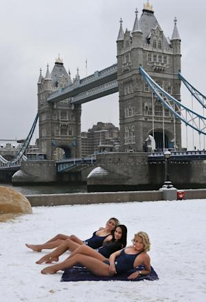 Backdropped by the iconic Tower Bridge, models is swimsuits pose for the photographers on a pop-up 'beach' amid the snow, during a photo-opportunity to promote a hotel chain, by the river Thames in London, Monday, Jan. 21, 2013. Hundreds of fights were canceled in Britain, France and Germany Monday as snow and ice blanketed Western Europe. London's Heathrow airport canceled about 130 flights, 10 percent of the daily total, compared to 20 percent on Sunday.(AP Photo/Lefteris Pitarakisp