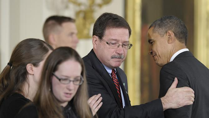The family of slain Sandy Hook Elementary School psychologist Mary Sherlach accepts the 2012 Presidential Citizens Medal, the nation's second-highest civilian honor, on her behalf posthumously from President Barack Obama, Friday, Feb. 15, 2013, during a ceremony in the East Room of the White House in Washington. Accepting the award is her husband, Bill Sherlach, and daughters, Katy Sherlach and Maura Schwartz. (AP Photo/Susan Walsh)