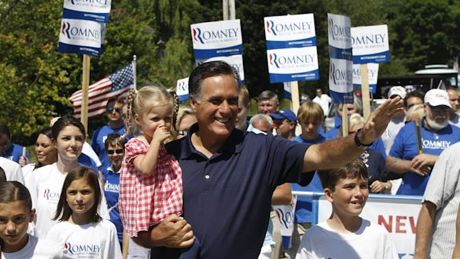 Republican presidential candidate, former Massachusetts Gov. Mitt Romney, carries his granddaughter Soleil, 3, as he participates in the Fourth of July Parade in Wolfeboro, N.H., Wednesday, July 4, 2012. (AP Photo/Charles Dharapak)