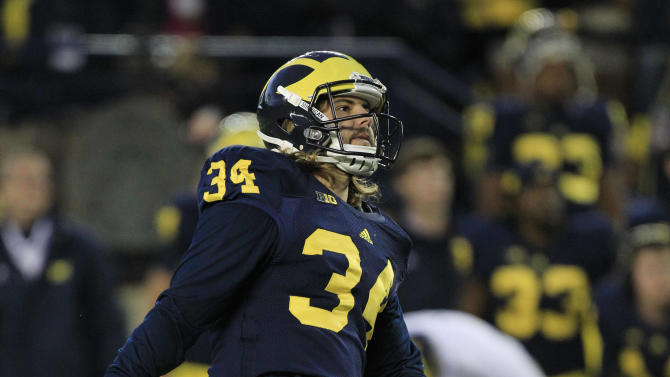Michigan kicker Brendan Gibbons (34) and placeholder Drew Dileo (9) watch as Gibbons game-winning field goal clears the posts with seconds remaining to defeat Michigan State in an NCAA college football game in Ann Arbor, Mich., Saturday, Oct. 20, 2012. (AP Photo/Carlos Osorio)