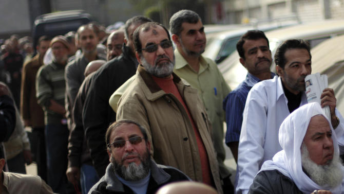 Egyptians wait to cast their votes outside a polling station during a referendum on a disputed constitution drafted by Islamist supporters of President Morsi in Cairo, Egypt, Saturday, Dec. 15, 2012. Egyptians were voting on Saturday on a proposed constitution that has polarized their nation, with Morsi and his Islamist supporters backing the charter, while liberals, moderate Muslims and Christians oppose it.(AP Photo/Khalil Hamra)