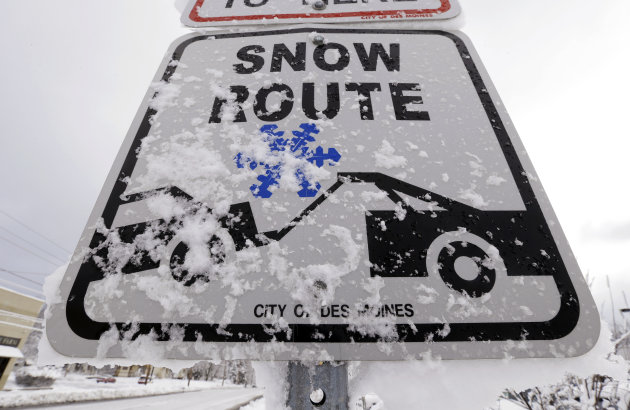 Snow clings to a Snow Route sign on a city street, Thursday, Dec. 20, 2012, in Des Moines, Iowa. The first widespread snowstorm of the season began a slow crawl across the Midwest on Thursday with som