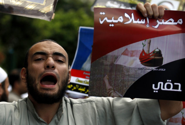 FILE - In this Friday, Sept. 23, 2011 file photo, an Egyptian man chants slogans and holds a poster that reads, in Arabic, &quot;Islamic Egypt,&quot; during a demonstration held by a Salafi group to protest the emergency law, in Tahrir Square in Cairo, Egypt. Under Mubarak, there were no mass killings along the lines of South African or some Latin American dictatorships in the 1980s. But tens of thousands of political prisoners were detained under emergency laws that expired last week after 31 years in force. Torture was systematic, and often extreme, and corruption was completely endemic. (AP Photo/Khalil Hamra, File)
