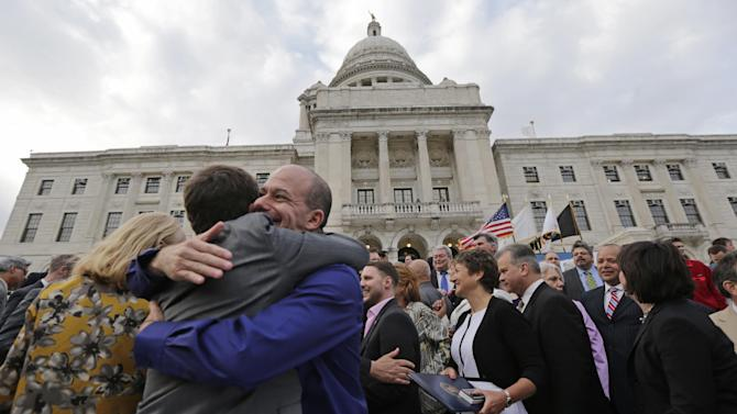 FILE - In this May 2, 2013, file photo two men embrace after a gay marriage was signed into law outside the State House in Providence, R.I. Three states and three countries have approved same-sex unions in just the two months since the Supreme Court heard arguments on the issue. Close observers on both sides of the divide are wondering whether such developments might affect the justices' consideration, particularly that of Justice Anthony Kennedy, which is likely to be decisive. (AP Photo/Charles Krupa, File)