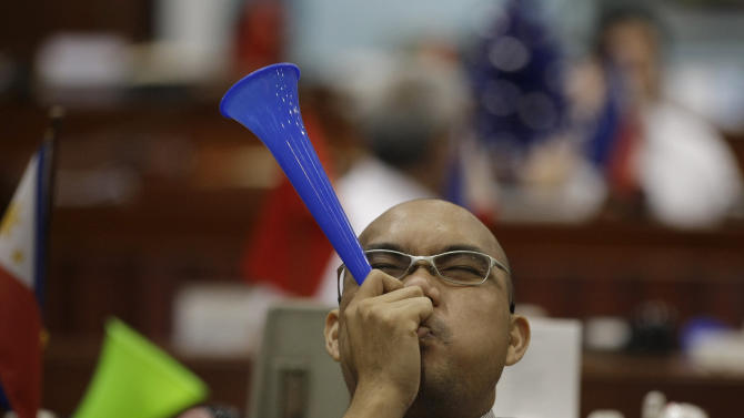 A Filipino trader blows a horn during the first day of trading at Philippine Stock Exchange at the financial district of Makati, south of Manila, Philippines on Wednesday Jan. 2, 2013. Stock markets in Asia registered relief Wednesday over the U.S. congressional vote to stop hundreds of billions of dollars in automatic tax increases and spending cuts that risked plunging the world's biggest economy into recession. (AP Photo/Aaron Favila)
