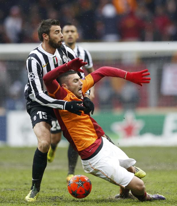 Balzagli of Juventus tackles Yilmaz of Galatasaray during their Champions League soccer match in Istanbul