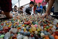 Customers sort through glass beads used to make jewellery at a market in Beijing. China's trade surplus widened to $26.7 billion in August as exports remained weak and imports registered a surprise fall, data showed Monday