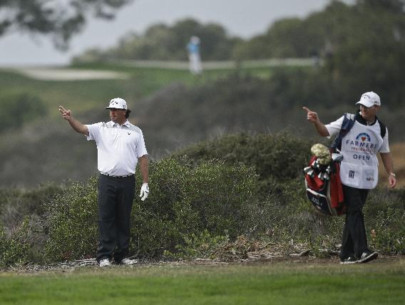 Pat Perez, left, and his caddie point to where Perez should drop his ball after hitting his tee shot into a canyon on the North Course at Torrey Pines during the second round of the Farmers Insurance
