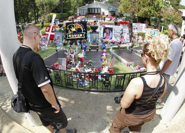 FILE -- This Aug. 2010 photo shows tourists viewing the grave of Elvis Presley at Graceland, Presley's home in Memphis, Tenn. Graceland opened for tours on June 7, 1982. They sold out all 3,024 tickets on the first day and didn't look back, forever changing the Memphis tourist landscape while keeping Elvis and his legend alive.(AP Photo/Mark Humphrey)