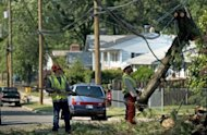 <p>Workers remove parts of a fallen tree from a telephone line July 1, 2012 in Hyattsville, Maryland. On Monday, more than 400,000 homes and businesses in and around Washington still lacked power in the aftermath of fierce thunderstorms and hurricane-like winds late Friday in the national capital region.</p>