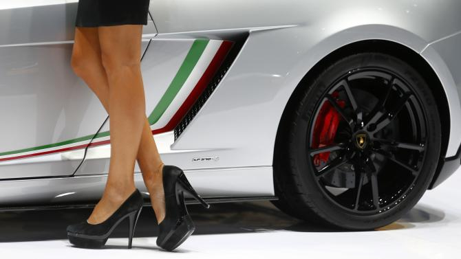 A model poses next to a Lamborghini Gallardo during a media preview day at the Frankfurt Motor Show (IAA)