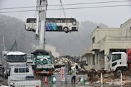 <p>A bus is removed from a roof of a building in Ogatsu district in Ishinomaki, Miyagi prefecture on March 10, 2012. Politicians from the devastated northeast repeatedly express exasperation at the slow pace of reconstruction after the tsunami and a lack of leadership from Tokyo.</p>